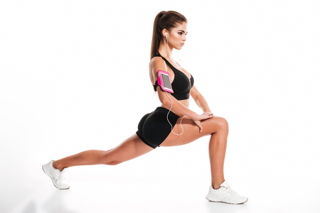 Side view portrait of a young pretty sportswoman doing squats and listening to music isolated on a white background
