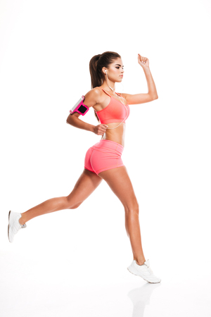 Side view of a sexy young fitness woman running isolated on the white background