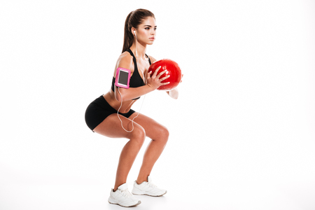 Side view portrait of a young pretty sportswoman doing squats with heavy fitness ball and listening to music isolated on a white background Stock Photo