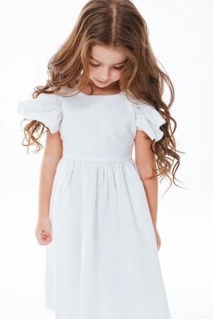 Sad cute little girl with long curly hair standing and looking down over white background