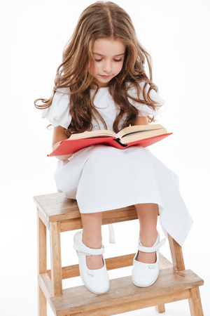 Cute curly little girl sitting and reading book over white background
