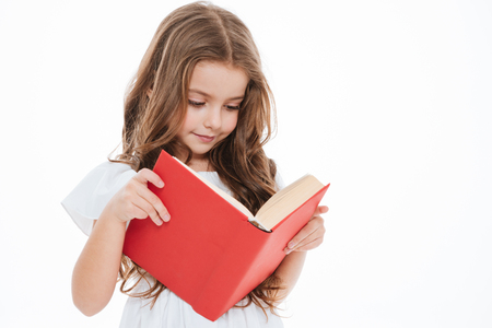 Lovely little girl standing and reading book over white background