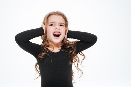 Irritated curly little girl covered her ears by hands and shouting over white background Stock Photo