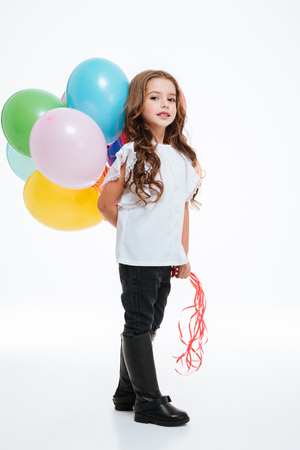 Full length of beautiful little girl standing and holding colorful balloons behind her over white background Stock Photo - 74173842