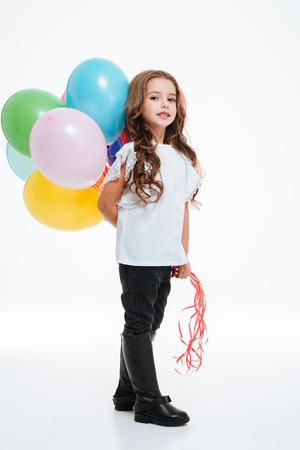 Volledige lengte van mooi meisje die en kleurrijke ballons zich achter haar bevinden houden over witte achtergrond Stockfoto