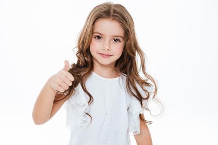 幸せなかわいい女の子立って、白い背景の上に親指を表示