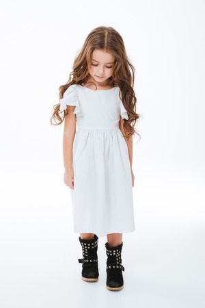 Sad tired little girl with curly long hair walking and looking down over white background Stock Photo