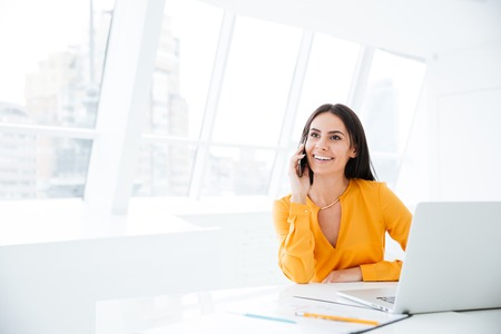 전화로 얘기하고 사무실에서 테이블에 앉아 웃는 비즈니스 여자 스톡 콘텐츠
