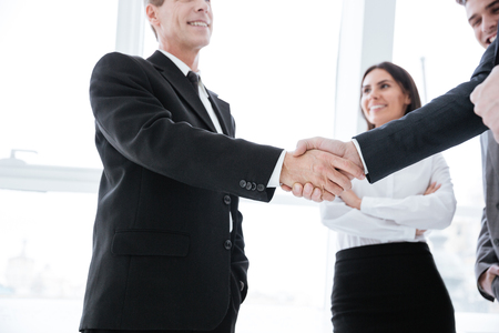 Business people shaking hands near the window in office with business woman on background. From below view Stock Photo