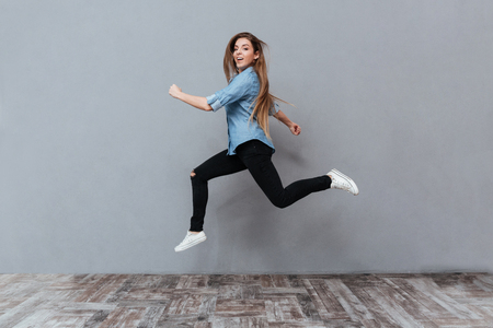 Full length image of Funny Woman jumping with open mouth in studio and looking at camera. Isolated gray background