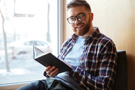 post secondary schools: Portrait of a smiling happy male student holding book and looking at camera while sitting on windowsill in library Stock Photo