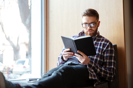post secondary schools: Young male student sitting on windowsill in library and reading book