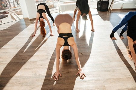 in unison: Top view of group of people working out and practicing yoga in studio