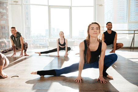 Group of happy young people working out in yoga studio