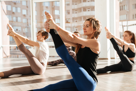 Group of happy young people sitting and stretching legs in yoga studio