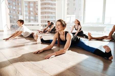 Group of smiling young people stretching and doing twine on the floor in yoga studio
