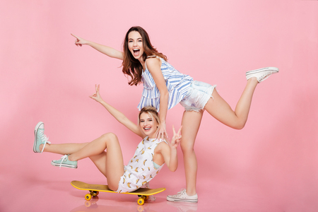 Two cheerful young women on skateboard pointing away and having fun over pink background Stock Photo
