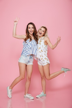 Full length of two happy young women standing and showing peace sign over pink background Stock Photo