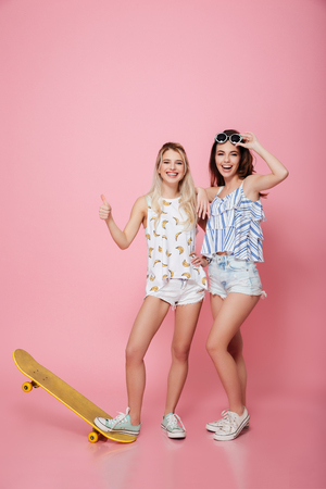 skateboarder: Two smiling young women with skateboard standing and showing thumbs up over pink background Stock Photo
