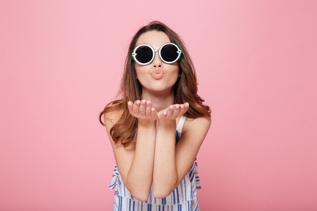 Cute lovely young woman in round sunglasses standing and sending kiss over pink background Stockfoto