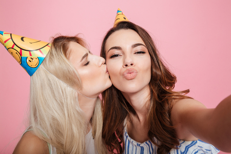 Two happy beautiful young women in birthday hats kissing and talking selfie over pink background Stock Photo