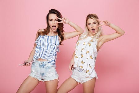 Two happy playful young women listening to music from smartphones and dancing over pink background Stock Photo