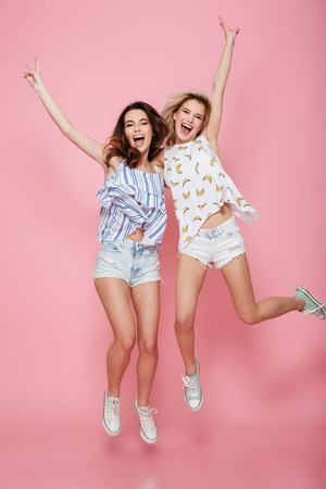 Full length of two cheerful young women showing victory sign and jumping over pink background Banco de Imagens