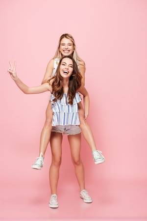 Photo of two pretty women standing isolated over pink background. Make peace gesture. Stock Photo