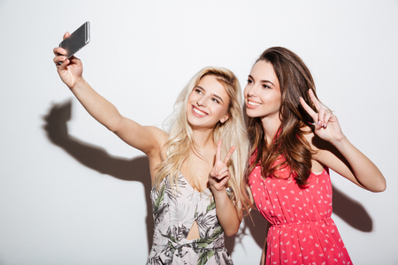 niñas sonriendo: Portrait of a happy two smiling girls making selfie photo on smartphone and showing two fingers sign on white background Foto de archivo