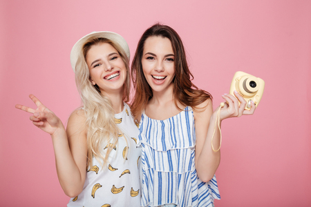 Two cheerful lovely young women standing and holding photo camera over pink background Stok Fotoğraf