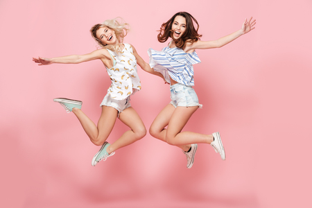 Two happy joyful young women jumping and laughing together over pink background