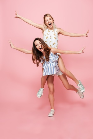 Image of two funny playful women standing isolated over pink background.