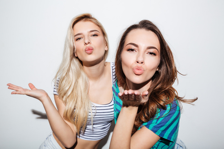Portrait of two beautiful young girls blowing kisses to camera isolated on the white background Stock Photo
