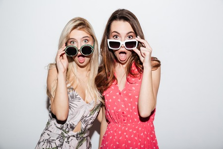 Portrait of attractive young shocked women looking at camera through eyeglasses isolated on a white background