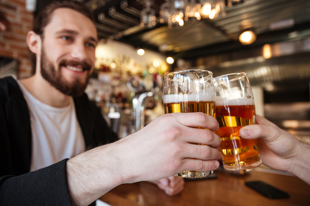 Cropped image of smiling man clinking glasses with friend on bar