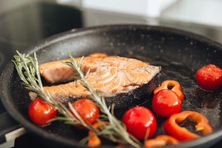 Photo of fish and vegetables on frying pan in kitchen. Cooking concept.