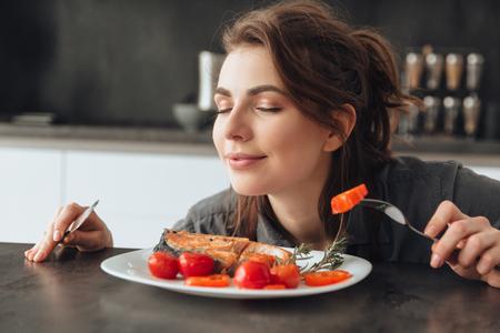 Bild der recht jungen Frau, die in der Küche beim Essen sitzt und riecht Fische und Tomaten. Augen geschlossen. Standard-Bild