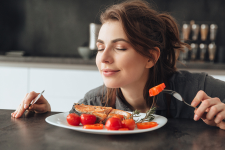 Image of pretty young woman sitting in kitchen while eating and smells fish and tomatoes. Eyes closed. Фото со стока