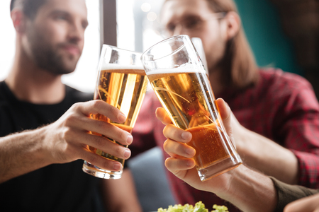Image of young friends sitting in cafe while drinking alcohol. Focus on glasses of beer. Stock Photo