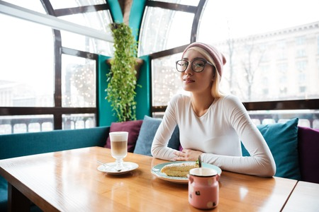 Beautiful young woman in hat and glasses drinking coffee and eating cake in cafe Stock Photo