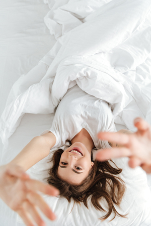 Image of young happy lady dressed in white t-shirt lies on bed at home indoors while stretching. Reklamní fotografie - 74564910
