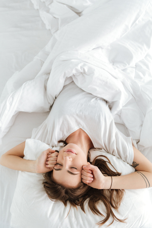 Image of young pretty woman dressed in white t-shirt lies on bed at home indoors while stretching. Stock Photo