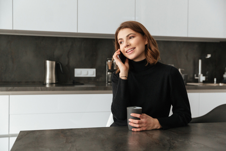devouring: Image of young smiling lady dressed in black sweater sitting at kitchen. Talking by mobile phone. Stock Photo