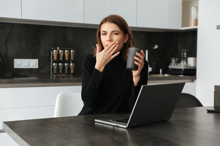 devouring: Image of young tired lady dressed in black sweater sitting at kitchen holding cup of coffee. Chatting by laptop and yawning.