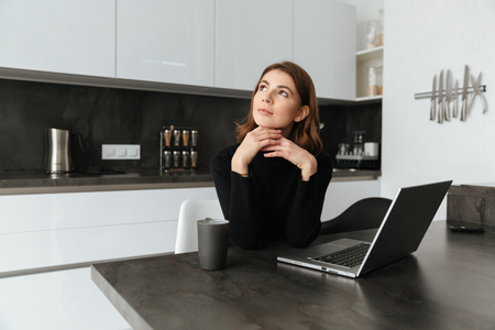 devouring: Image of young thoughtful woman dressed in black sweater sitting at kitchen. Chatting by laptop. Looking aside.