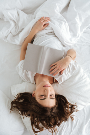 Top view of tired young woman with book lying and sleeping in bed
