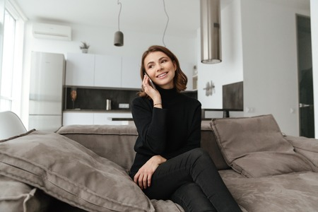 devouring: Photo of young cheerful woman dressed in black sweater sitting on sofa at kitchen. Talking by mobile phone.