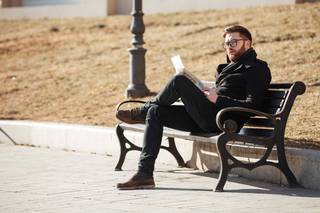 Pensive bearded young man sitting on bench and reading newspaper outdoors