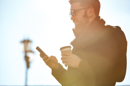 Smiling bearded young man using mobile phone and drinking coffee outdoors Фото со стока