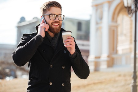 biz: Happy bearded young man talking on cell phone and drinking coffee in the city